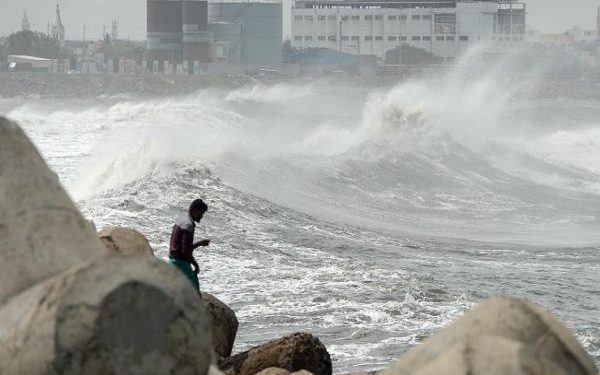 A man looks out as waves hit a breakwater at Kasimedu fishing harbour in Chennai on May 19, 2020, as Cyclone Amphan barrels towards India's eastern coast. (Photo by Arun SANKAR / AFP)