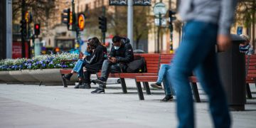A man wearing a protective face mask checks his cell phone as he sits on a bench in Stockholm on May 4, 2020 during the new coronavirus Covid-19 pandemic. (Photo by Jonathan NACKSTRAND / AFP) (Photo by JONATHAN NACKSTRAND/AFP via Getty Images)