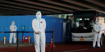 Staff members in protective suits stand guard next to a bus before the expected arrival of a World Health Organisation (WHO) team tasked with investigating the origins of the coronavirus disease (COVID-19) pandemic, at Wuhan Tianhe International Airport in Wuhan, Hubei province, China January 14, 2021. REUTERS/Thomas Peter
