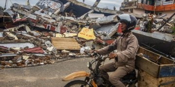 epaselect epa08942953 A man rides his motorbike past collapsed houses in the aftermath of an earthquake in Mamuju, West Sulawesi, Indonesia, 17 January 2021. At least 56 people were killed and hundreds injured after a 6.2 magnitude earthquake struck Sulawesi island on 15 January.  EPA-EFE/IQBAL LUBIS