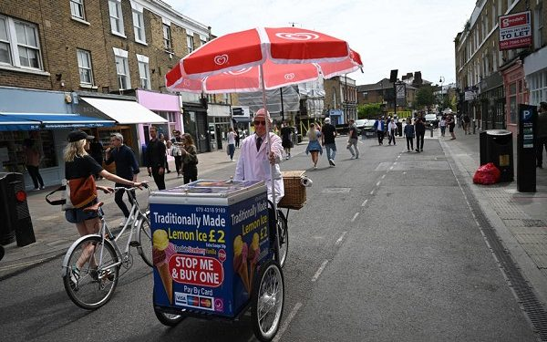 epa08428317 Ann ice-cream seller ride his bike on Broadway Market in east London, Britain, 17 May 2020. Boris Johnson continues his plan to reopen Britain after weeks of measures to stem the spread of the SARS-CoV-2 coronavirus which causes the Covid-19 disease. People who can't work from home are now actively encouraged to return to workplaces, but use of public transport is being discouraged. More outdoor activity is allowed, as is meeting one person from another household under limited circumstances.  EPA-EFE/NEIL HALL