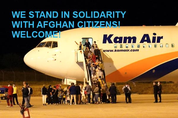 """Фото: МИА, стоп кадар од преносот во живо на пристигнувањето на цивилите од Авганистан, 30.08.2021. Пораката """"Ние сме солидарни со граѓаните од Авганистан. Добредојдовте!"""" е од ЦИВИЛ, организација која прва им посака добредојде на авганистанските цивили."""
